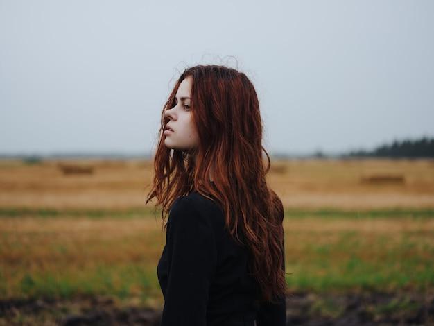 フィールド風景ポーズで黒のドレスを着た赤髪の女性