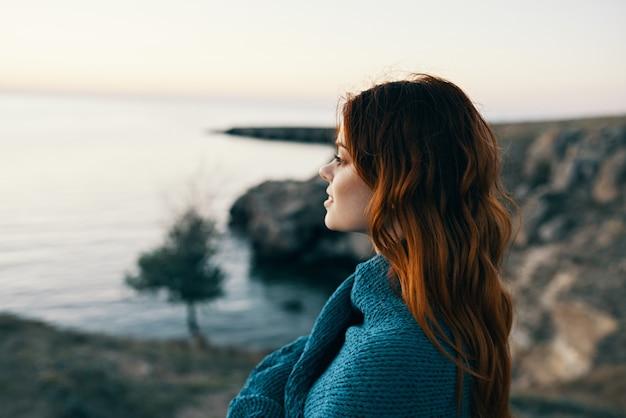 日没時に湖の赤毛の女性