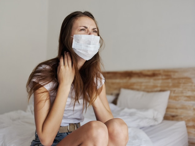 ベッド隔離コロナウイルスに座っている医療マスクルームの赤毛の女性