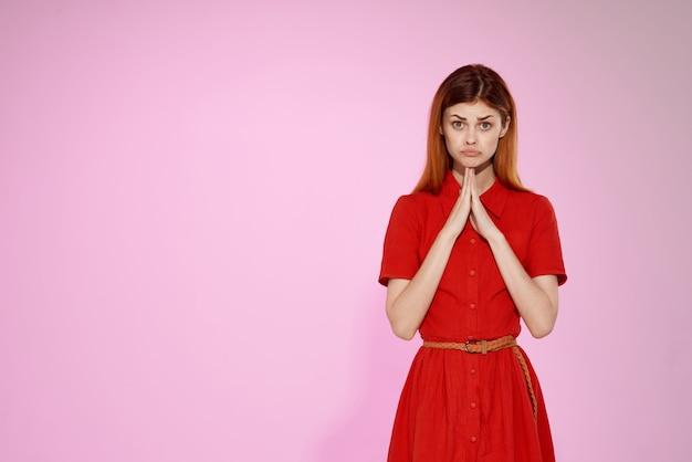 赤いドレスファッションエレガントなスタイルのピンクの背景の赤髪の女性