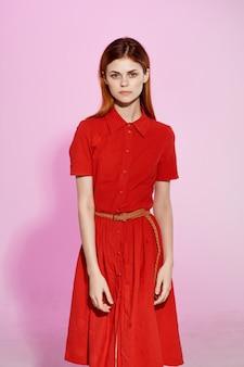 Рыжая женщина в красном платье жесты рук роскошный розовый фон