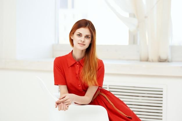 椅子のファッションに座っている赤いドレスを着た赤毛の女性
