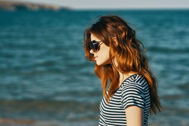 Рыжая женщина в солнцезащитных очках на пляже у синего моря и гор на заднем плане