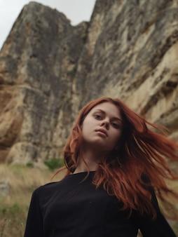 山の中で赤毛の女性は自然のロマンスを揺るがす