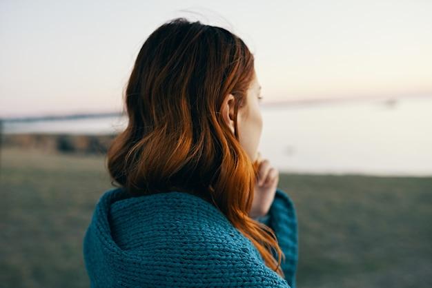 彼女の肩に青い格子縞の後ろの景色と山の赤毛の女性