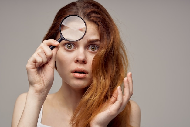 Redhaired woman magnifier near the face hygiene closeup