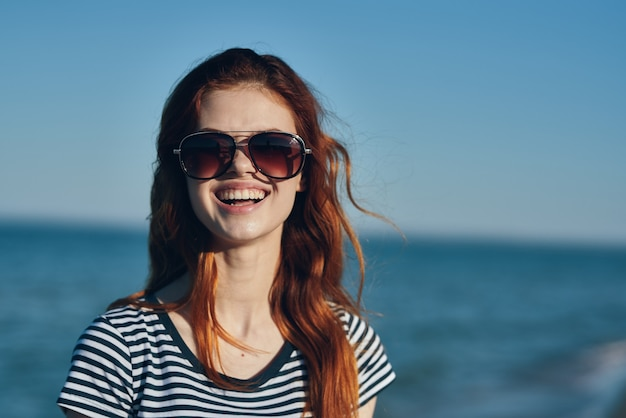 T シャツとサングラスの海を背景に夏休みの赤毛の女性モデル