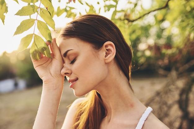木の緑の近くの赤毛の女性は夏の魅力を残します