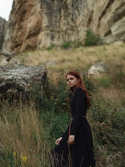 山の上の赤毛の女性は休暇のライフスタイルを歩きます