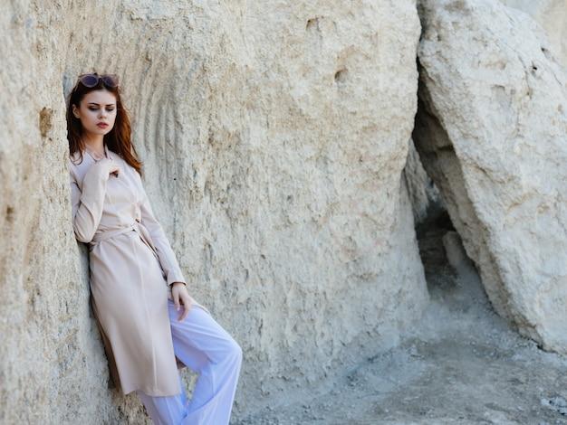 岩の自然の休息をポーズする赤毛の女性