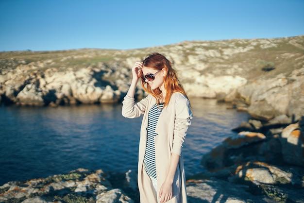 赤毛の女性が自然の正面モデルで川の近くの山を旅する
