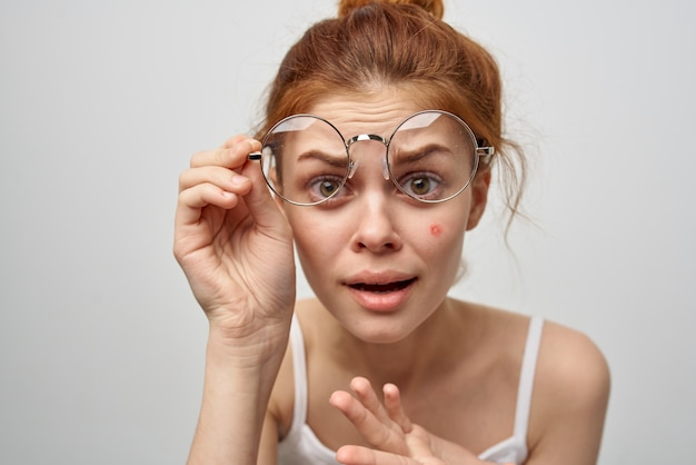 Redhaired woman wearing glasses pimple on face dermatology skin care