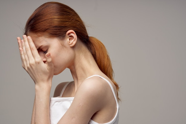 Redhaired woman in a white tshirt pimples on the face light background