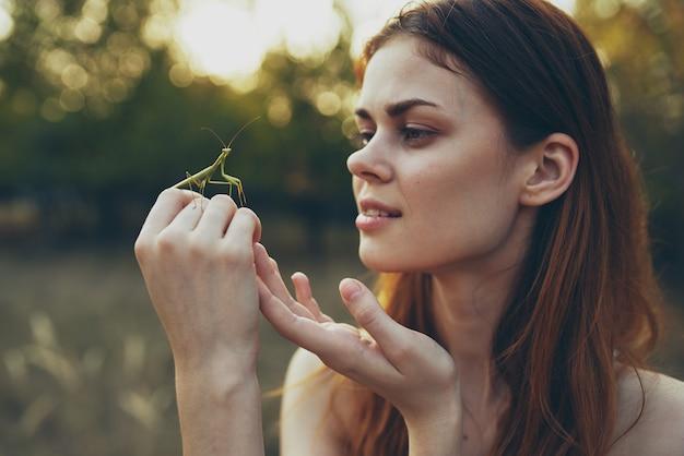 野生の自然を手にカマキリを持った赤毛の女性