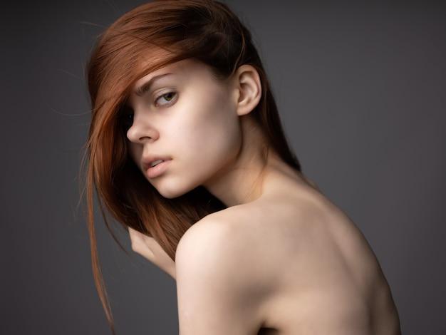 스튜디오 포즈 벌거 벗은 어깨와 redhaired 여자