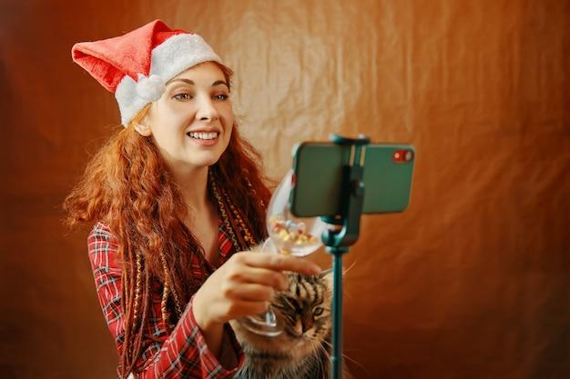 サンタの帽子と猫の赤毛の女性がスマートフォンでガラスをチリンと鳴らし、友達やあなたと仮想的に話している...