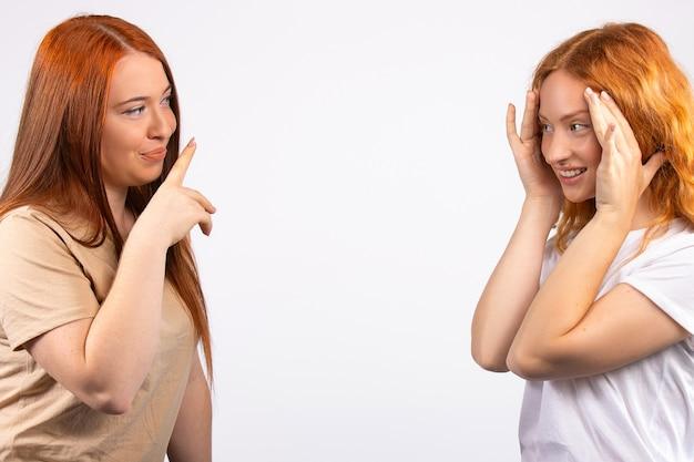 Redhaired 여자 친구 얼굴을 만들고 빈 공간이있는 흰 벽 위에 재미있는 사진을 찍는 바람둥이