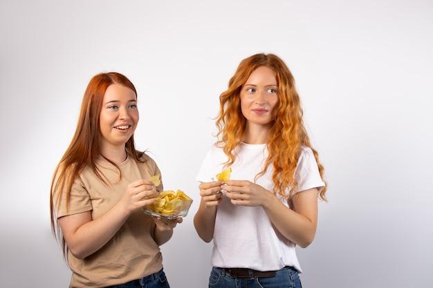 흰 벽에 칩의 유리 그릇을 가진 redhaired 여성은 옆으로보고 미소 공간