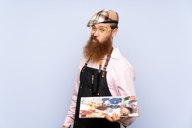 Redhead artist man with long beard holding a palette with sad expression