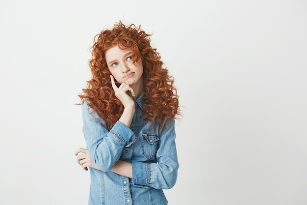 Redhead attractive girl thinking . copy space.
