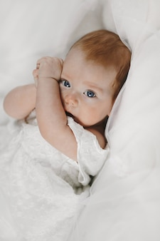 Redhead baby girl is lying on the white blanket with big clear blue eyes, and covering face with tiny arms