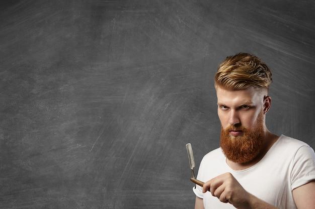 Рыжий парикмахер со стильной стрижкой и хипстерской бородой держит свой аксессуар для парикмахерской - старинную опасную бритву.
