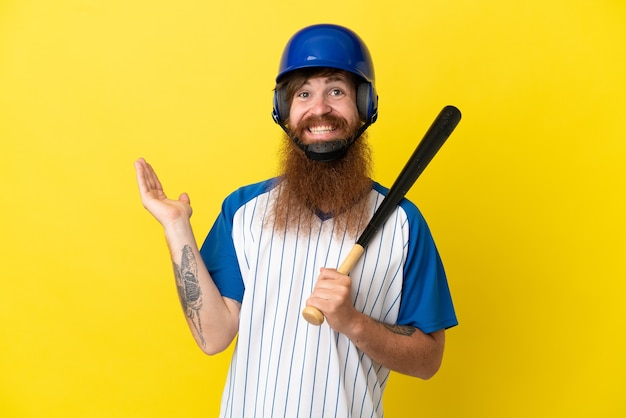 Redhead baseball player man with helmet and bat isolated on yellow background extending hands to the side for inviting to come