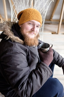 Redhead bearded man in polar jacket holding cup of hot coffee or tea and smiling