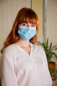 Рыжая красивая девушка в защитной повязке на лице
