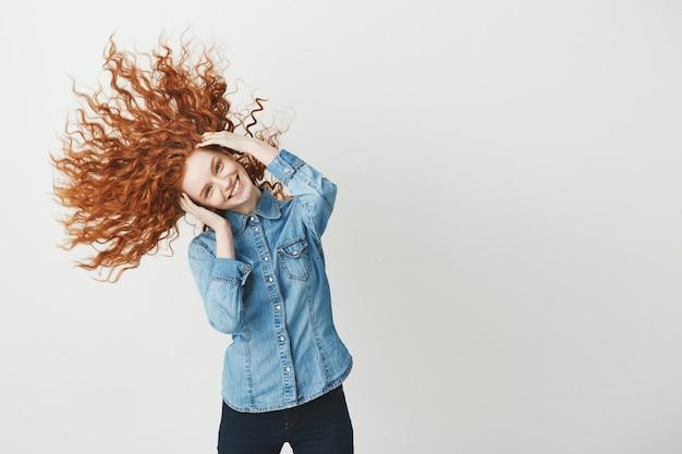 Рыжая красивая девушка улыбается улыбающийся тряся вьющимися волосами