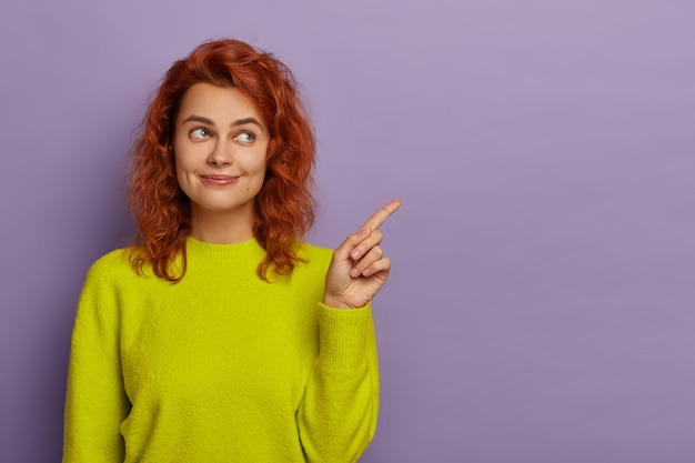 Redhead beautiful woman points index finger aside, dressed in bright yellow jumper, demonstrates copy space for your advertising content or promotion, suggests using blank place for information