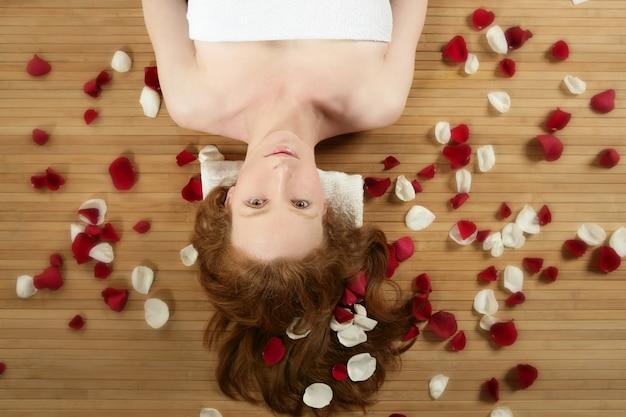 Redhead beautiful woman, rose petals on hair