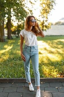 흰색 스 니 커 즈에 유행 선글라스 유행 청바지에 세련 된 티셔츠에 빨간 머리 아름 다운 젊은 hipster 여자는 따뜻하고 화창한 여름 날에 공원에서 산책.