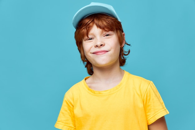 Redhead boy boy with a grin on his face blue cap yellow t-shirt planning something bad