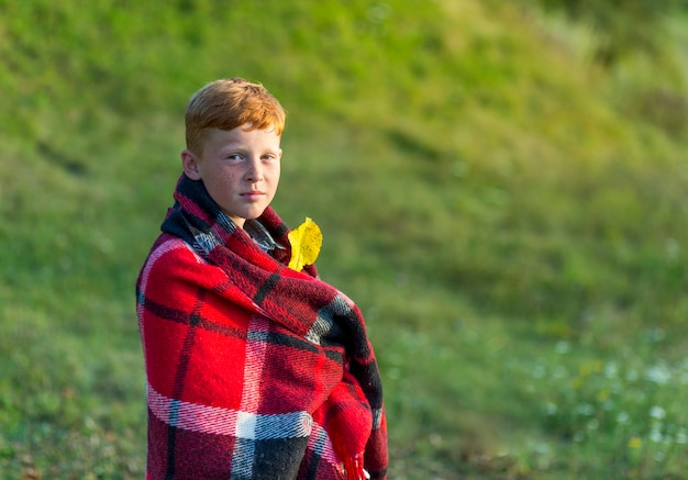 Redhead boy covered with blanket