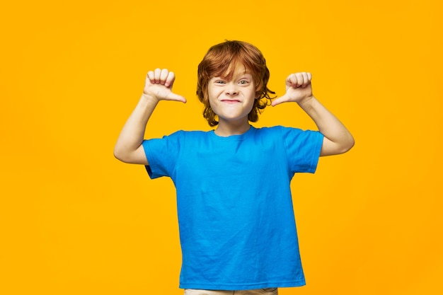 カメラに顔をゆがめ、彼の手で怒っている顔の表情の感情を身振りで示す赤毛の少年