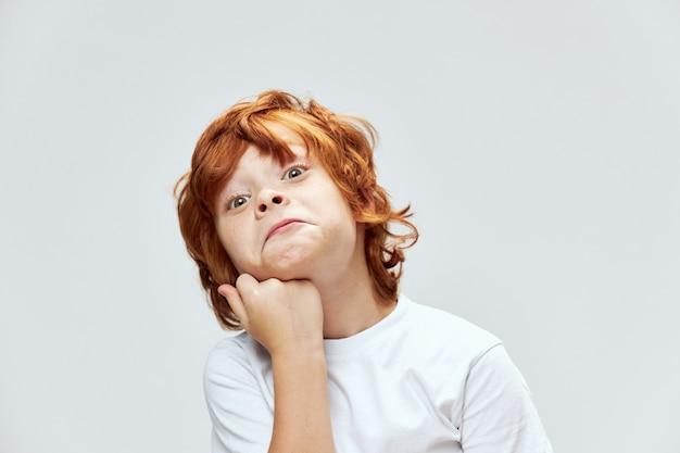 顔のスタジオの近くの手のクローズアップトリミングされたビューを顔をゆがめている赤毛の少年