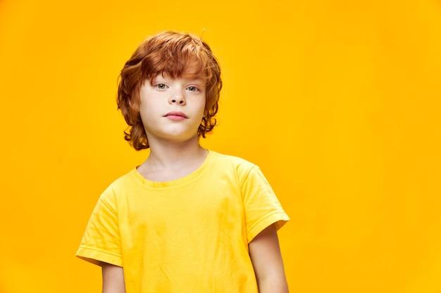 Рыжий мальчик в желтой футболке на изолированном фоне смотрит вперед обрезанный вид