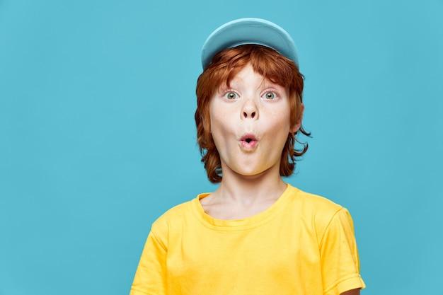 Redhead boy surprised facial expression blue cap yellow t-shirt studio