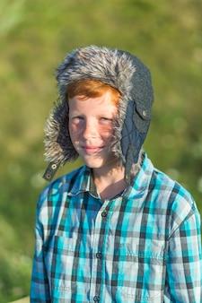 Redhead boy wearing a fur cap