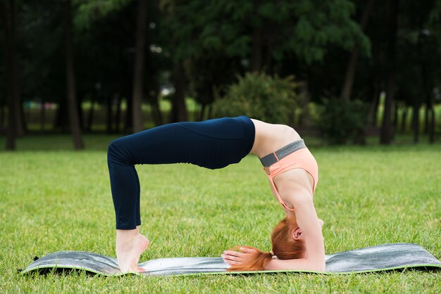 Redhead caucasian girl standing in a bridge pose on a mat on the grass in the park