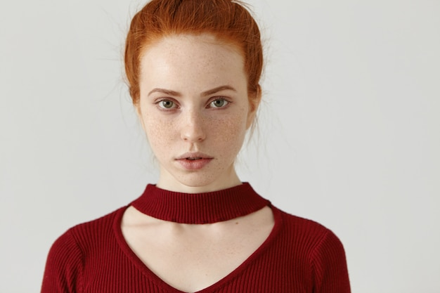 Redhead caucasian girl with pretty face with freckles wearing trendy red dress with cut out neck, modeling isolated