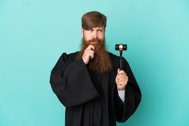 Redhead caucasian judge man isolated on blue background having doubts and thinking