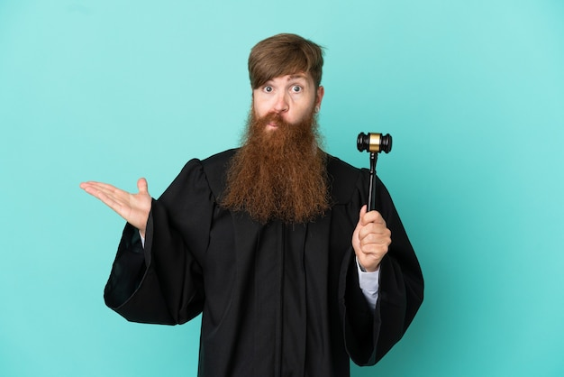 Redhead caucasian judge man isolated on blue background having doubts while raising hands