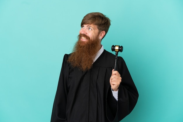 Redhead caucasian judge man isolated on blue background looking to the side and smiling