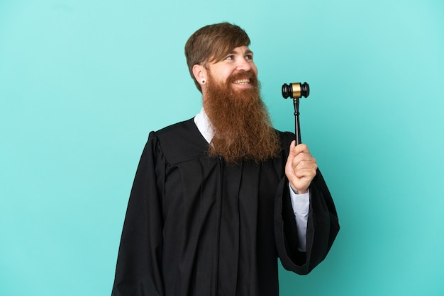 Redhead caucasian judge man isolated on blue background looking side