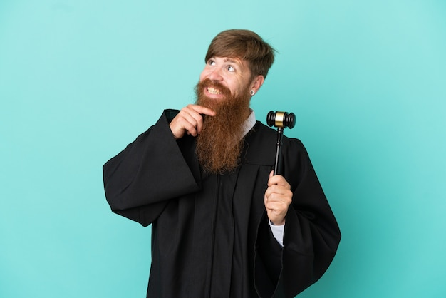 Redhead caucasian judge man isolated on blue background looking up while smiling