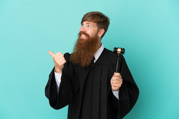 Redhead caucasian judge man isolated on blue background pointing to the side to present a product