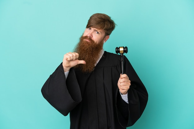 Redhead caucasian judge man isolated on blue background proud and self-satisfied