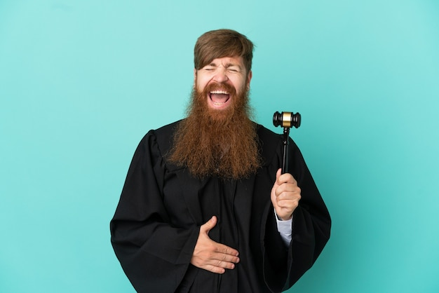Redhead caucasian judge man isolated on blue background smiling a lot